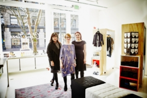 three women standing close to each other inside a shop